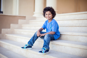 A portrait of smiling kid boy sitting on stages outdoor. Children and emotions concept