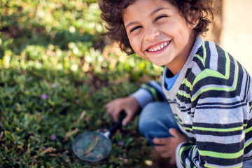 A kid boy looking through magnifier at plants. Children, discovery and botany concept