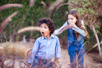Two happy kids boy and girl playing outdoor. Childhood and emotions concept.