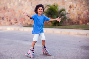 Smiling kid boy roller skate in the park. Children and activity concept
