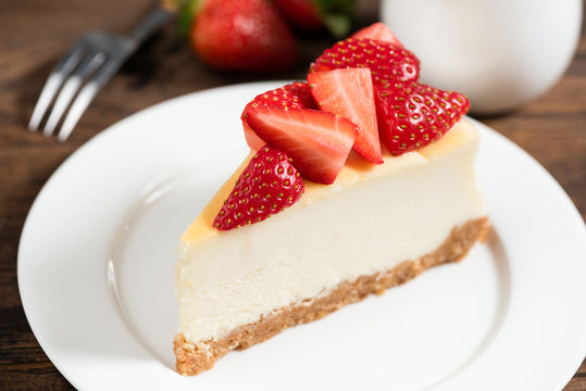 Cheesecake slice with strawberries. Plain classical New York cheesecake decorated with fresh strawberry slices. Tasty dessert