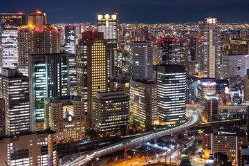 Japan. Osaka. Evening panorama of the big city. View of Osaka business center from a height. Buildings with glowing Windows and roads. Cities of Japan. Modern urban architecture.