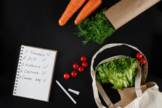 Fresh vegetables and a shopping list on a black background. Carrots, tomatoes, dill, lettuce and canvas bag. Eco friendly responsible consumption.