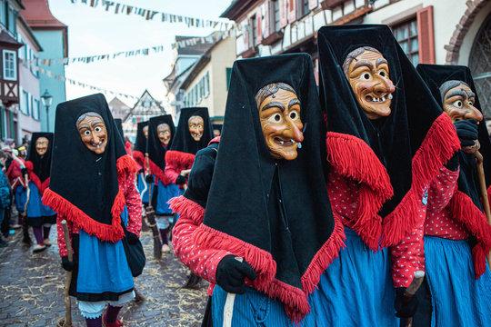 Troepfle Hexen aus Bad Rippoldsau - Hexen im blau rotem Gewand mit großen schwarzen Kopfhauben marschieren selbstbewusst nach Vorne. Bei Fastnachtumzug in Staufen Süd Deutschland.