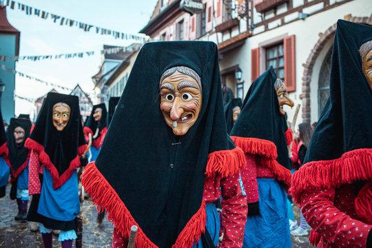 Troepfle Hexen aus Bad Rippoldsau - Hübsche Hexe mit schwarzer Kopfhaube und rot, blauem Gewand. Bei Fastnachtumzug in Staufen Süd Deutschland.