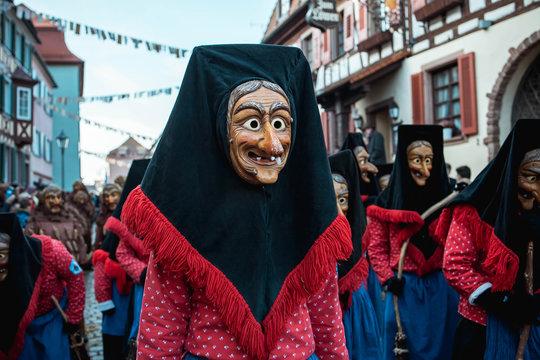 Troepfle Hexen aus Bad Rippoldsau - Hübsche Hexe mit schwarzer Kopfhaube und rot, blauem Gewand schaut schüchtern zur Seite. Bei Fastnachtumzug in Staufen Süd Deutschland.