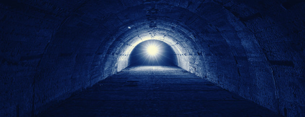 Panoramic image of tunnel with light in end in Phantom Blue trendy color.