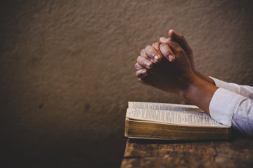 Hands folded in prayer on a Holy Bible in church concept for faith Fotomurales
