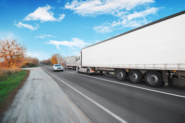 A big truck and trailer with other vehicles driving fast on the countryside road against a blue sky with clouds Wall mural