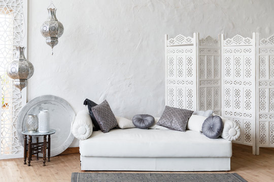 Eastern traditional interior. Romantic interior with comfortable authentic sofa. Exotic relaxation room. Arabic living room in white color with white sofa. White decorative wood panel on plaster wall