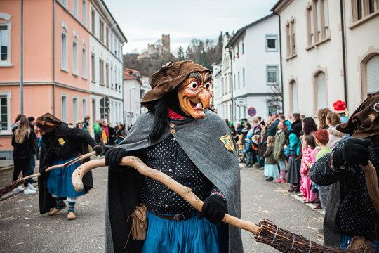 Schlosshexe aus Buchholz - Lustige Hexe mit großen Augen und langer Nase vor schöner Stadtkulisse und einer Burg im Hintergund. Bei Fastnachtumzug in Waldkirch Süd Deutschland.