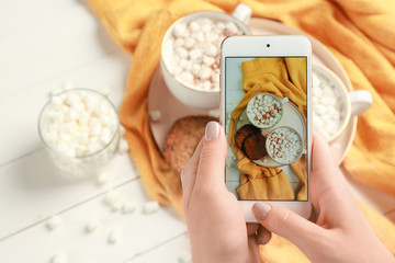 Female food photographer with mobile phone taking picture of hot chocolate with marshmallows
