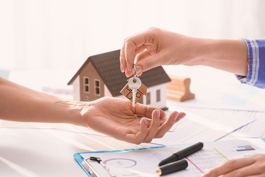 Real estate agent giving a key from new house to client in office