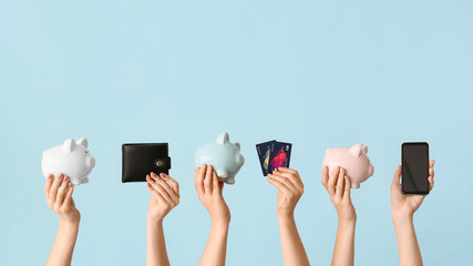 Female hands with piggy banks, credit cards, wallet and mobile phone on color background. Concept...