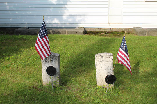 Two gravestones at an old cemetery in Bar Harbor, Maine with US flags
