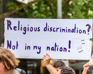 A white political protest banner with blue lettering is being held at a religious discrimination street rally