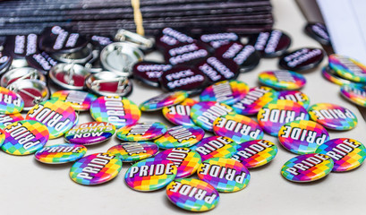 A pile of 'Pride' campaign buttons or badges are scattered on a table at a religious discrimination political protest