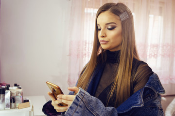 Portrait of young beautiful woman caucasian girl using mobile smart phone camera to text message call or photo while standing in a room at home