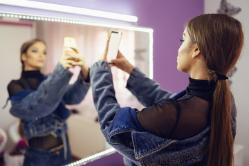 Portrait of young beautiful woman caucasian girl using mobile smart phone camera to take a selfie photo while standing in a room at home in front of the mirror makeup