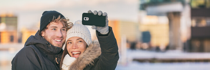 Aufkleber - Selfie couple happy winter travel walk tourists taking photo with phone on city street panorama lifestyle. Asian woman, Caucasian man wearing knit hats and jackets.