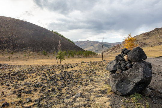 The beautiful landscape of Mongolia near the Khorgo extinct volcano. Khorgo is a small volcano in central Mongolia surrounded from barren landscape. stony ground and colorful trees in Autumn