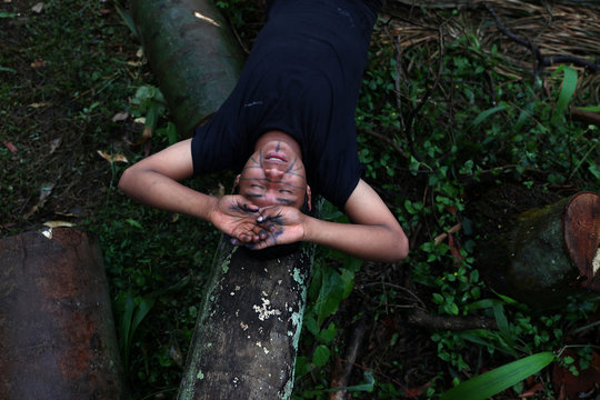A Guarani Mbya indigenous man sings while laying on a tree trunk in an occupied area as they protest against tree cutting and the construction of an apartment complex near Jaragua indigenous land in Sao Paulo
