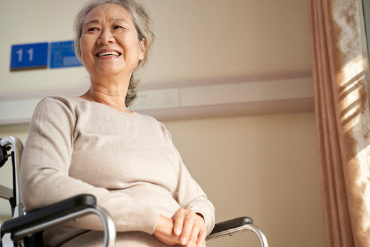 happy old woman sitting in wheelchair in nursing home