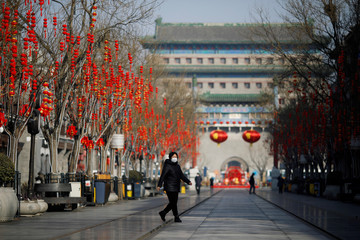 Woman wearing a face mask walks on the Qianmen pedestrian street in the morning after the extended Lunar New Year holiday caused by the novel coronavirus outbreak, in Beijing