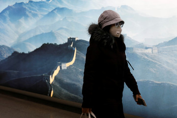 Woman wearing a face mask walks past a sign with an image of the Great Wall at a subway station in the morning after the extended Lunar New Year holiday caused by the novel coronavirus outbreak, in Beijing