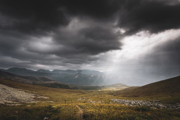 Mountain landscape. A ray of the sun breaks through the clouds