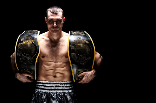 Kickboxing world middleweight champion stands with two belts. The concept of a healthy lifestyle, victory, success. Motivation.