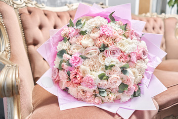 Beautiful bouquet of mixed flowers on a vintage sofa. the work of the florist at a flower shop. Delivery fresh cut flower. European floral shop.