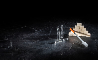 Bottle of insulin for diabetes and injection syringe, healthcare concept with refined loaf sugar cubes on dark background