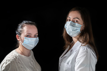 Two womans in protective mask on dark background