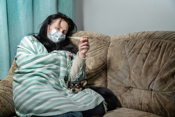 Sick young woman in bed at home having flu, measuring temperature
