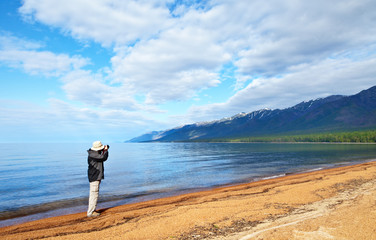 Baikal Lake. A tourist photographs a beautiful morning landscape with snowy peaks of the mountains of the Holy Nose Peninsula on the sandy shore of the Barguzin Bay. Summer travels on the lake
