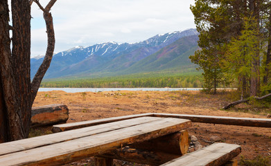 Lake Baikal. Convenient tourist parking with wooden tables and benches is equipped in a nature park on the beautiful sandy shore of Barguzin Bay. Summer travel