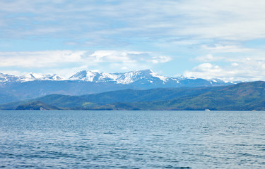 Beautiful natural background with snowy mountain peaks and forested hills on the shore of the Chivyrkuisky Bay of Lake Baikal on a June day