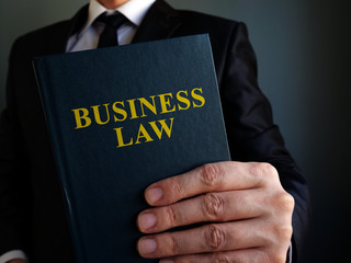 Businessman is holding business law book.