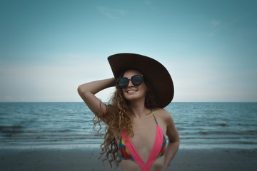 Pretty beautiful woman in bikini with sunglasses and hat over tropical beach, sea and sky, Summer holiday concept