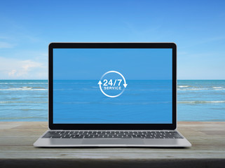 24 hours service flat icon with modern laptop computer on wooden table over tropical sea and blue sky with white clouds, Business full time service online concept