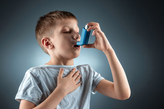 Portrait of a boy using an asthma inhaler to treat inflammatory diseases, shortness of breath. The concept of treatment for cough, allergies, respiratory tract disease.