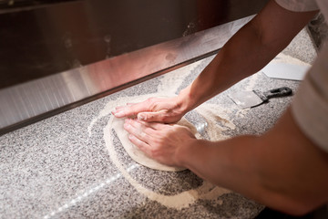 Dough for Neapolitan pizza, the chef rolls out the blanks. Closeup hand of chef baker in uniform white apron cook pizza at kitchen