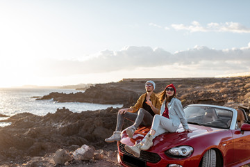 Printed roller blinds Deep brown Young lovely couple enjoying landscapes, sitting together on a car hood, traveling by car on the rocky ocean coast. Carefree lifestyle, love and travel concept