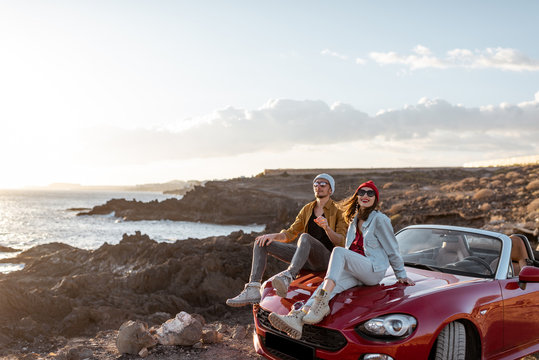 Young lovely couple enjoying landscapes, sitting together on a car hood, traveling by car on the rocky ocean coast. Carefree lifestyle, love and travel concept