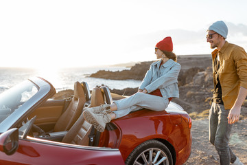 Young joyful couple having fun on the rocky coast while traveling by car on a sunset. Carefree lifestyle, love and travel concept