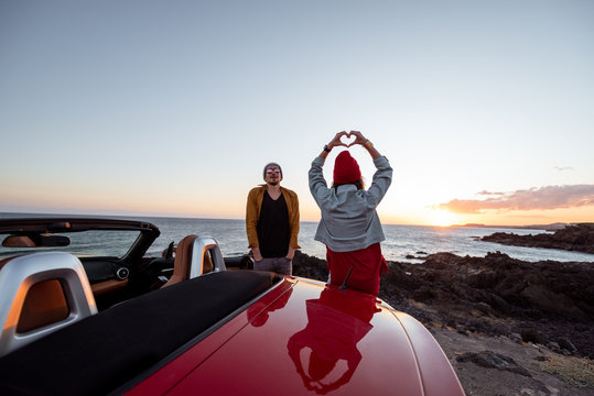 Couple enjoying beautiful views on the ocean, standing together near the car on the rocky coast, showing with hands heart shape. Carefree lifestyle, love and travel concept