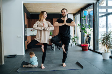 Parents standing in vrksasana position while their child plays next to them