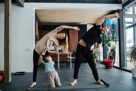 Parents doing side tilts while their infant child seeking attention