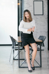 Portrait of beautiful businesswoman holding laptop and pen, smiling and looking at camera while standing in modern office.
